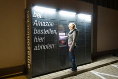 En kvinna använder en amasonskåpstation som lokaliseras bredvid en Aldi supermarket arkivbilder