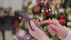 En kvinna använder en bärbar grej för att beskåda sociala nätverk, medan rymma en smartphone i hennes händer mot de ljusa ljusen stock video