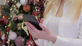 En kvinna använder en bärbar grej för att beskåda sociala nätverk, medan rymma en smartphone i hennes händer mot de ljusa ljusen lager videofilmer