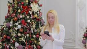 En kvinna använder en bärbar grej för att beskåda sociala nätverk, medan rymma en smartphone i hennes händer mot de ljusa ljusen arkivfilmer