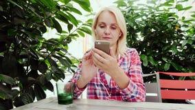En kvinna använder en smartphone i ett hemtrevligt kafé Sitter på en terrass under gröna buskar, staden av Graz i Österrike arkivfilmer