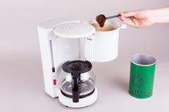 En kvinna använder kaffepulvret in i filterpåse Royaltyfri Bild