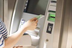 En kvinna använder en kreditkort på en ATM på gatan Operation med pengar betalning kopiera avstånd royaltyfri fotografi