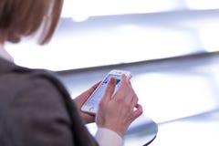 En kvinna använder en mobiltelefon Arkivbilder