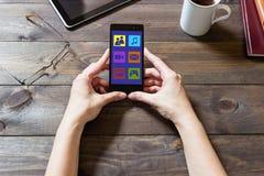 En kvinna använder sociala nätverk med en mobiltelefon Fotografering för Bildbyråer