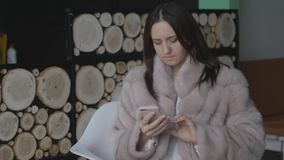 En kvinna använder en telefon, medan sitta i ett kafé och överför att vänta på ditt flyg stock video