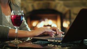 En kvinna arbetar med en bärbar dator nära spisen I ramen kan du se endast händer och ett närliggande exponeringsglas av vin lager videofilmer
