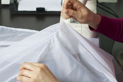 En kvinna arbetar på en symaskin Hon syr gardinerna på fönstret Royaltyfri Foto
