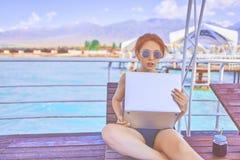 En kvinna arbetar på semester arkivbild