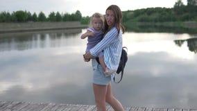 En kvinna bär lite flickan i hennes armar stock video
