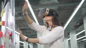 En kvinna bär VR-exponeringsglas och arbeten med att iscensätta projekt på ett bräde arkivfilmer