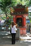 En kvinna ber framme av ett altare som installeras i borggården av en tempel i Saigon (Vietnam) Fotografering för Bildbyråer