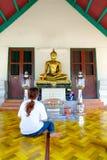 En kvinna ber till Buddhastatyn Arkivfoto