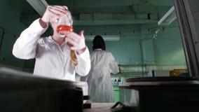En kvinna blandar en orange flytande arkivfilmer