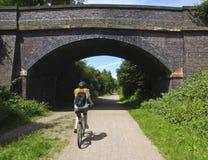 En kvinna cyklar den Wirral vägen, västra Kirby royaltyfria foton