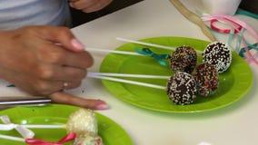 En kvinna dekorerar pilb?gar av fl?tad tr?dkakapop som ligger p? en platta Godis som dekoreras med olika f?rger f?r spridning lager videofilmer