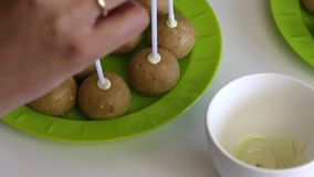En kvinna doppar hennes pinne in i sm?ltt vit choklad och fixar den i en popcakekubb Mellanrum lokaliseras p? plattan stock video