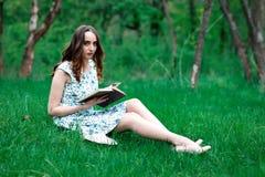 En kvinna eller en flicka i en klänning, med en bok i parkera, sitter på arkivfoto