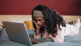 En kvinna får mycket ilsken och förargad, når han har mottagit meddelandet på hennes portative dator Hon ligger på sänghemmet arkivfilmer