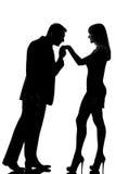 En kvinna för hand för parman kyssande Arkivbild