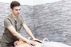 En kvinna f?r ett varmt stenar massage p? en brunnsort arkivbild