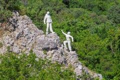 En kvinna frågar för hjälp från en man skulptur Arkivbild