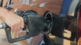 En kvinna fyller bensin din bil I ramen endast är synliga händer och att öppna gasbehållaren stock video
