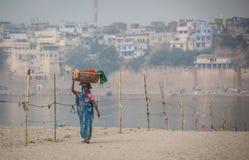 En kvinna går med tvättkorgen på hennes huvud arkivfoton