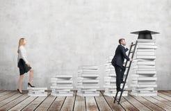 En kvinna går upp att använda trappa som göras av vita böcker för att nå avläggande av examenhatten, medan en man har funnit en g arkivfoton