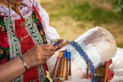 En kvinna gör att snöra åt för spole - folkkonst Fotografering för Bildbyråer