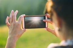 En kvinna gör ett foto på en smartphone Arkivfoto