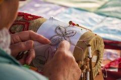 En kvinna gör spolen som snör åt Palickovanie Arkivbild