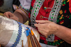En kvinna gör spolen som snör åt Palickovanie Arkivfoton