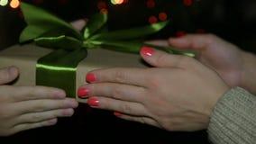 En kvinna ger en gåva för nytt år till ett barn En ask i hennes händer på bakgrunden av en bokeh arkivfilmer