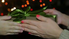 En kvinna ger en gåva för nytt år till ett barn En ask i hennes händer på bakgrunden av en bokeh stock video