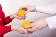 En kvinna ger gymnastikbollar till en gammal kvinna Arkivbild