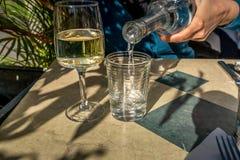 En kvinna häller vatten in i ett exponeringsglas bredvid ett exponeringsglas av vitt vin I Arkivfoto