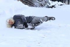 En kvinna halkade på vintervägen, avverkar ner och gör sig ont arkivfoton