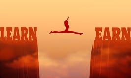 En kvinna hoppar mellan två klippor arkivfoto