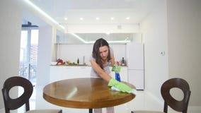 En kvinna i en åtsittande grå T-tröja med en djup urringning torkar ett stort köksbord med en trasa stock video