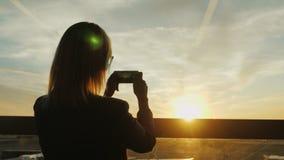 En kvinna i en affärsdräkt tar ett fotografi av en solnedgång i ett fönster I en kontorsbyggnad- eller flygplatsterminal arkivfoto