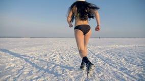 En kvinna i en baddräkt joggar över snö som en utbildningsrutin arkivfilmer