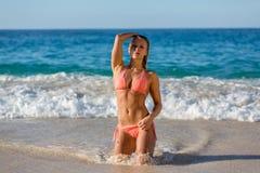 En kvinna i bikini på stranden Arkivfoto