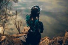 En kvinna i bilden av en fe och ett trollkvinnaanseende över en sjö i en svart klänning och en krona arkivbilder