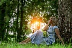 En kvinna i en bl? kl?nning som sitter n?ra ett tr?d och, beundrar solnedg?ngen royaltyfri bild