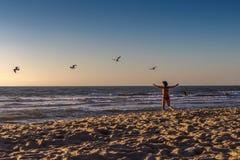 En kvinna i den röda baddräkten på stranden fotografering för bildbyråer