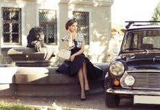 En kvinna i en retro klänning som poserar nära en bil arkivbilder