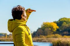 En kvinna i ett gult omslag, medan att resa ser i avståndet som skyddar solen med hennes hand_ royaltyfria foton