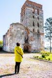 En kvinna i ett gult omslag ser den gamla building_en för den förstörda templet royaltyfria foton