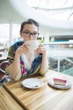 En kvinna i ett kafé dricker kaffe Royaltyfria Foton